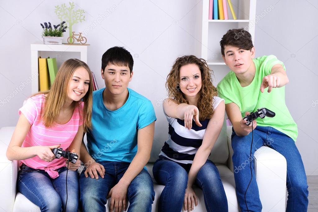 Grupo De Jovenes Amigos Jugando Juegos De Video En Casa Foto De