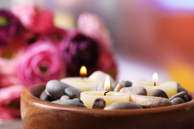 Composition with spa stones, candles  and flowers on  bamboo mat, on  bright background