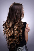 gyönyörű fiatal nő, hosszú haj, a szürke háttér