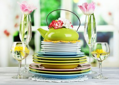 Stack of colorful ceramic dishes and flowers, on wooden table, on light background