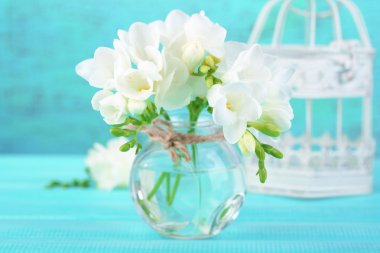 Beautiful freesia flowers, on blue wooden background