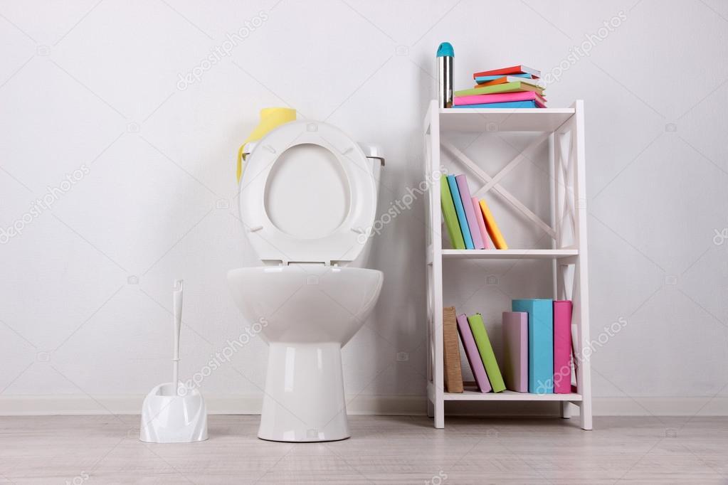 Witte wc pot en staan met boeken op een muur achtergrond kleur