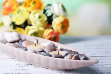 Composition with spa stones, candles  and flowers on color wooden table, on light background