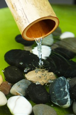 Spa still life with bamboo fountain and stones, close up