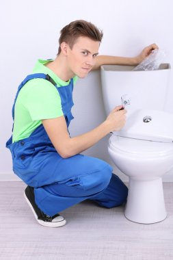 Plumber with toilet plunger on light background