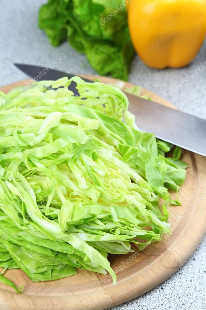 Chopped cabbage on wooden board, close-up, on kitchen table background