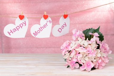 Happy Mothers Day message written on paper hearts with flowers on pink background stock vector