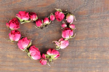 Heart of beautiful pink dried roses on old wooden background