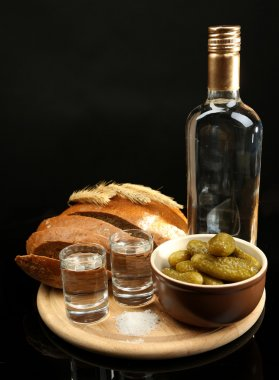 Composition with bottle of vodka, glasses, and marinated vegetables on wooden board, isolated on black