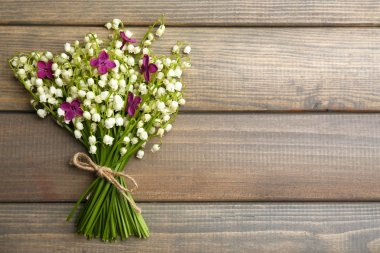 Beautiful lilac flowers and lilies of the valley, on wooden background