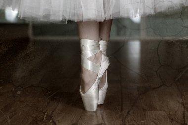 Ballerina legs in pointes in dark dancing hall