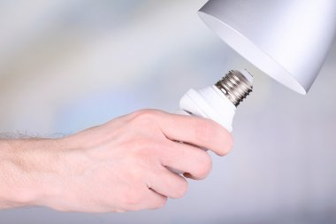 Hand changing light bulb for lamp at home