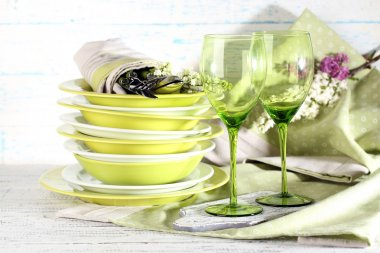 Green table settings, on table, on light background
