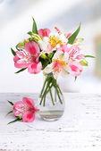 kosatců květiny ve váze na stole na světlé pozadí