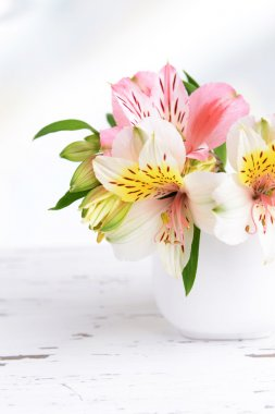 Alstroemeria flowers in vase on table on light background