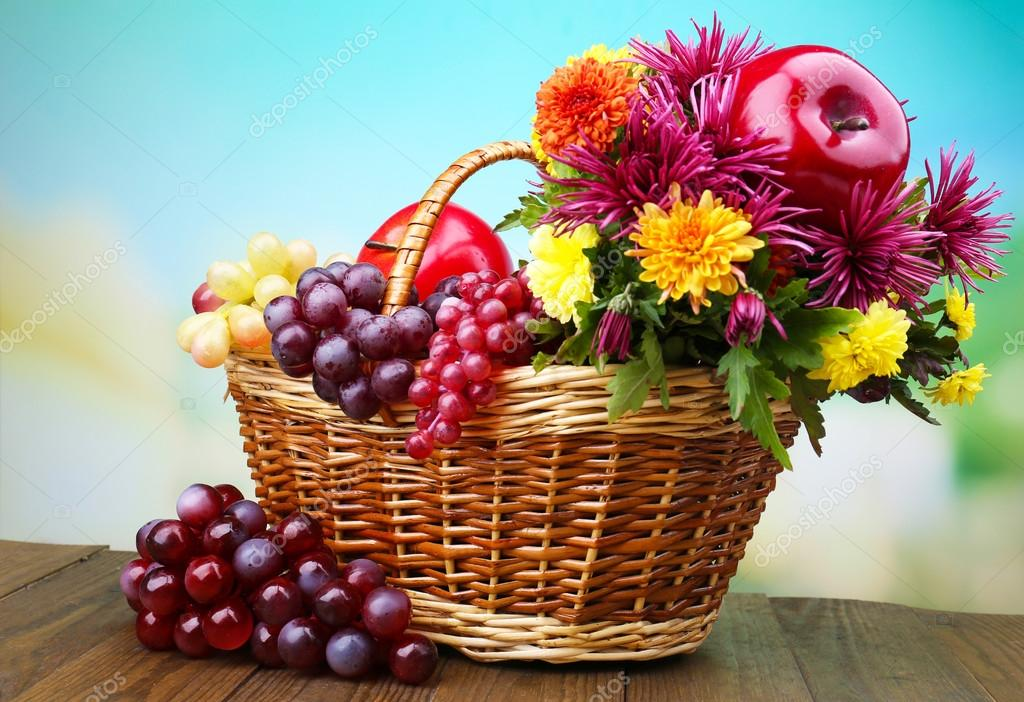 Composition With Beautiful Flowers In Wicker Basket And Fruits, On Bright  Background U2014 Photo By Belchonock