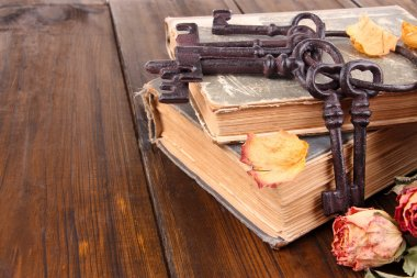 Beautiful composition with old key and old books on wooden background