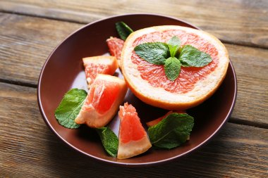 Ripe chopped grapefruit with mint leaves on plate, on wooden background