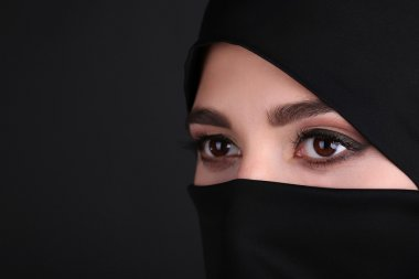 Beautiful muslim arabic woman in paranja on dark background