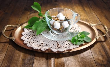 Glass cup with dry flowers and herbs, fruits ingredients for tea, on tray, on color wooden background