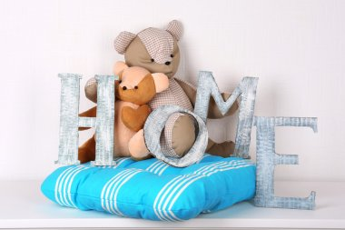 Decorative letters forming word HOME with teddy bear on wall background