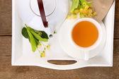 Fotografie Tasty herbal tea with linden flowers on wooden table