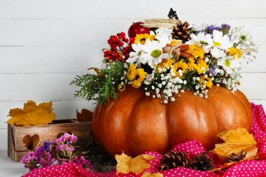 Beautiful autumn composition in pumpkin with decorative box on table on wooden background