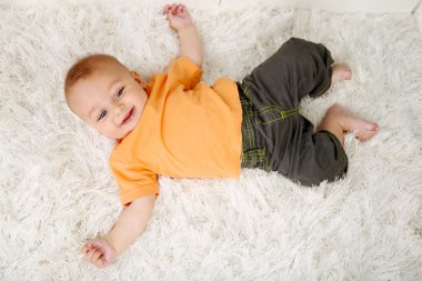 Cute baby boy lying on floor in room