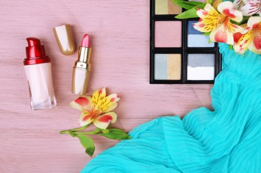 Eyeshadow, lipstick and flowers on color wooden background