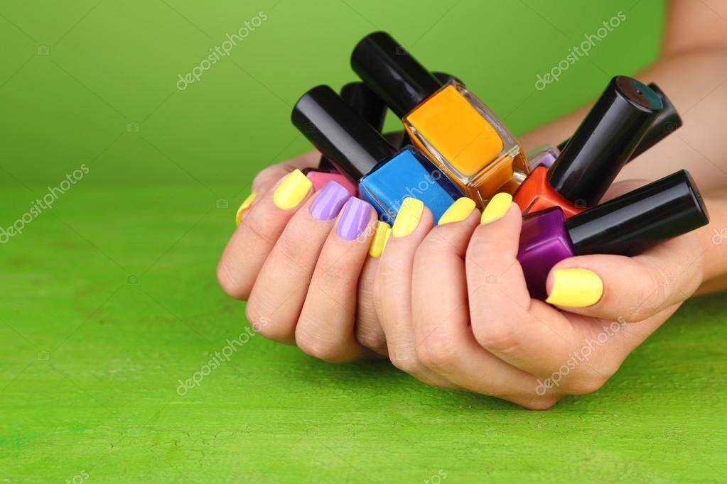 manos femeninas con clavos coloridos estilo sosteniendo botellas con ...