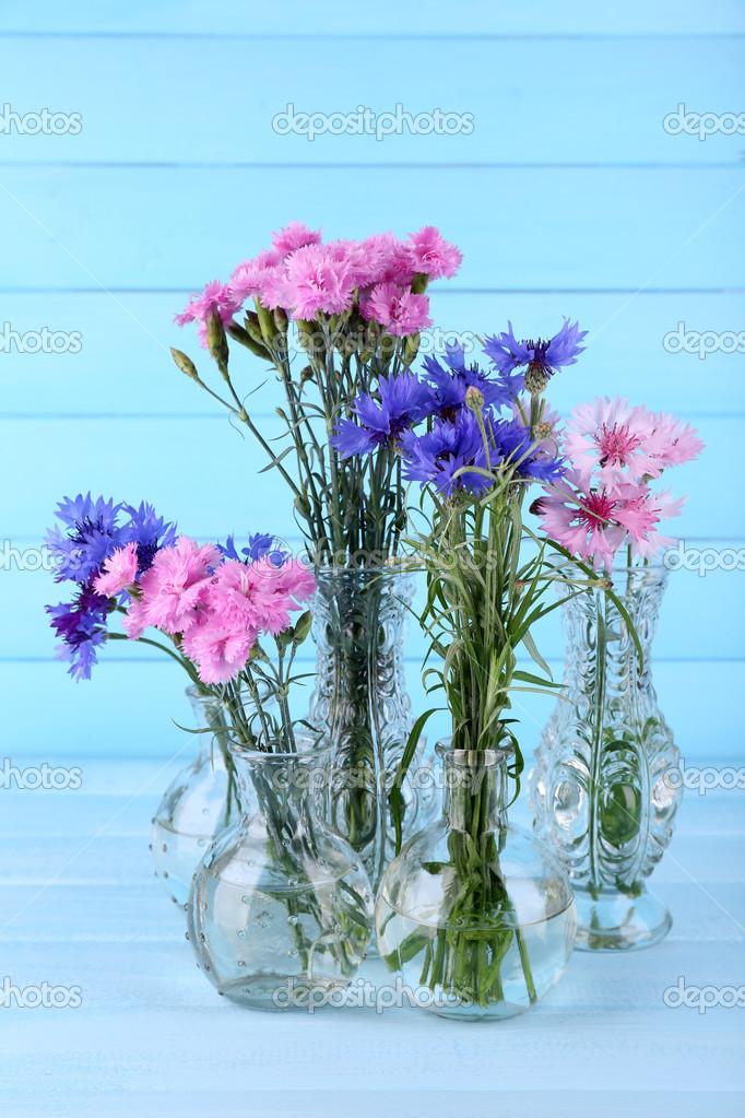 flores de verano hermoso en jarrones sobre fondo azul de madera u foto de stock