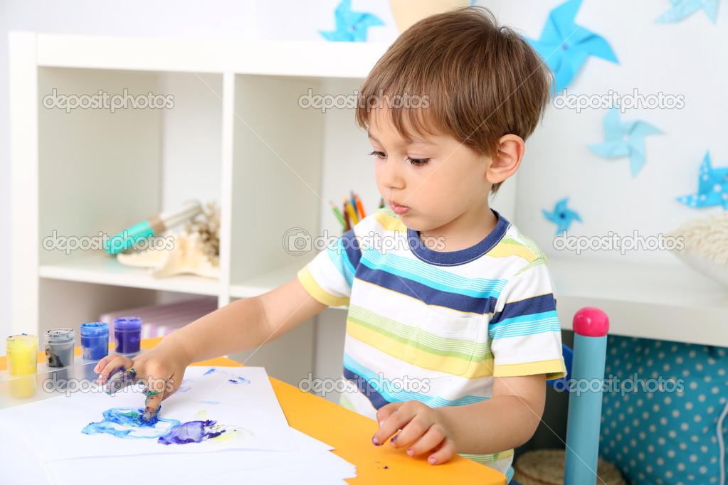 Schattige kleine jongen schilderij in kamer u stockfoto