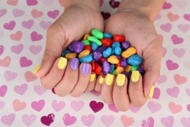 Female hand with stylish colorful nails holding colorful candies, on bright background