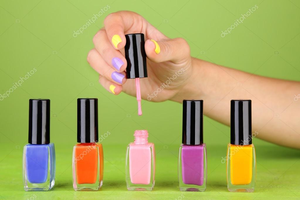 mano femenina con clavos coloridos estilo sosteniendo la botella con ...