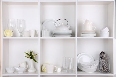 Different white clean dishes on wooden shelves