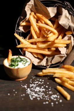 Tasty french fries in metal basket on wooden table with dark light