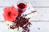 Hibiscus čaj a květin na barevný ubrousek na dřevěné pozadí