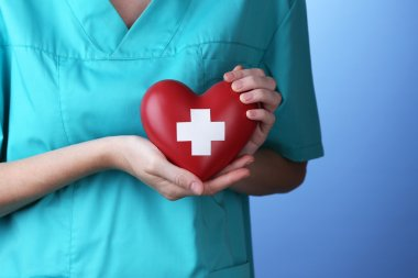 Red heart with cross sign in doctor hand, close-up, on color background