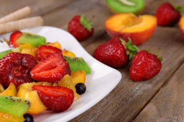 Fresh fruits salad with ice cream on plate and berries on wooden background