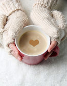 Fotografie Female hands with hot drink, on light background
