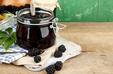 Tasty blackberry jam and fresh berries, on wooden table