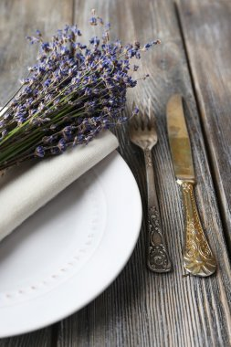 Dining table setting with lavender flowers on wooden table background