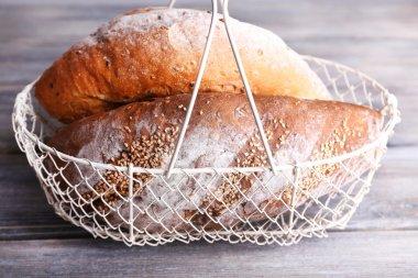 Fresh baked bread in basket, on wooden background
