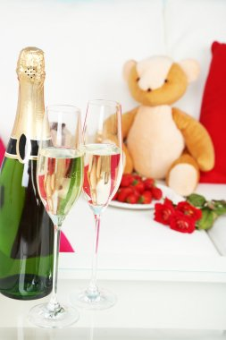 Romantic still life with champagne, strawberry and roses in room