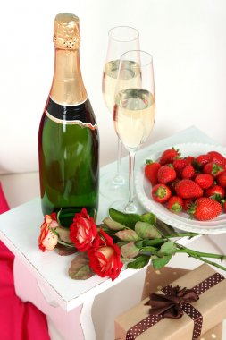 Romantic still life with champagne, strawberry and roses on sofa