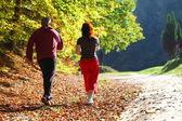 žena a muž běžecké stopy v podzimním lese