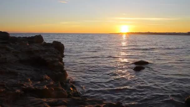 Skalnatá pláž při západu slunce