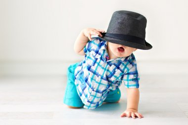 Cute baby sitting on the floor in a hat