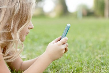Girl outdoors with a mobile phone