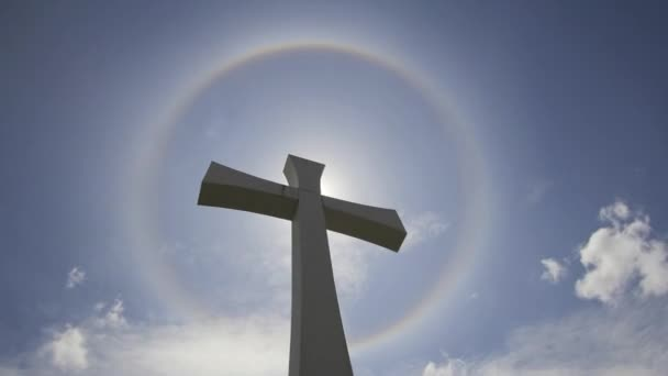 Crucifix Cross with Halo Sun Flare Timelapse with Moving White Clouds against Blue Sky 1080p